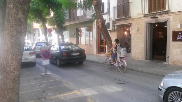 Una mujer transita en bicicleta este lunes por el centro de Dénia.